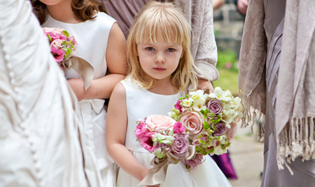 Bride and bridesmaid walking into church holding a beautiful bouquet of flowers